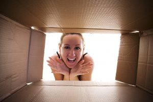 Young happy woman looking into cardboard box.